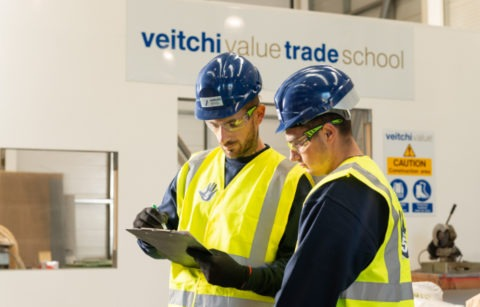Two Veitchi Apprentices check clipboard in Veitchi Value Trade School